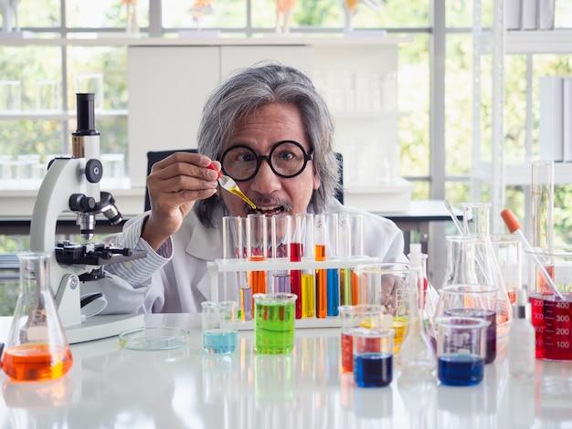 Wissenschaftlicher forscher asiens, der ein reagenzglas klare lösung in einem labor hält