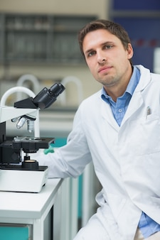 Wissenschaftlicher forscher mit mikroskop im labor