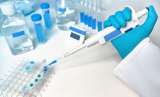 Wissenschaftlicher hintergrund in blau und weiß mit automatischer pipette