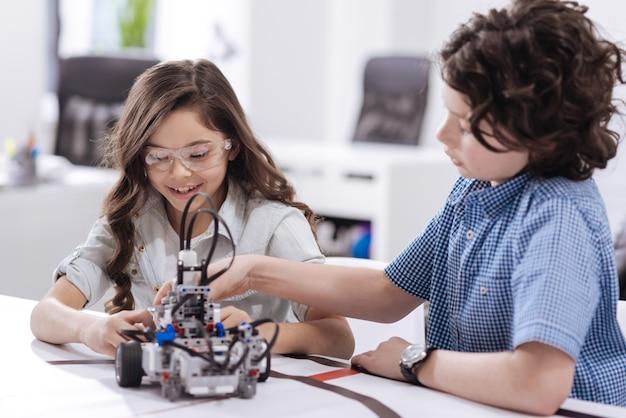 Wissenschaftliches abenteuer. erfreute glückliche qualifizierte kinder, die in der schule sitzen und roboter schaffen, während sie freude ausdrücken