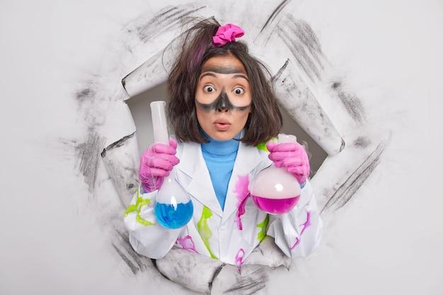 Wissenschaftsarbeiter hat überraschten ausdruck starrt verwanzte augen auf kamera hält zwei flaschen mit bunter flüssigkeit macht chemische experimente in wissenschaftlichen laborposen durch loch in papier