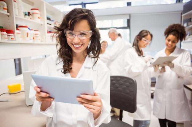 Wissenschaftskursteilnehmer, der tabletten-pc im labor hält