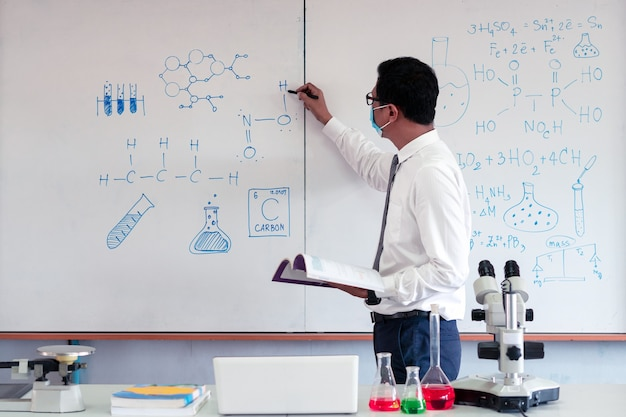 Wissenschaftslehrer, der im klassenzimmer mit tragender gesichtsmaske unterrichtet