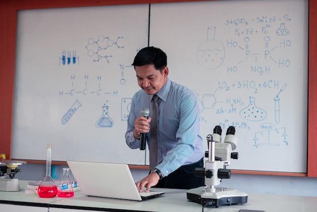 Wissenschaftslehrer, der maske trägt und online mit laptop im klassenzimmer unterrichtet