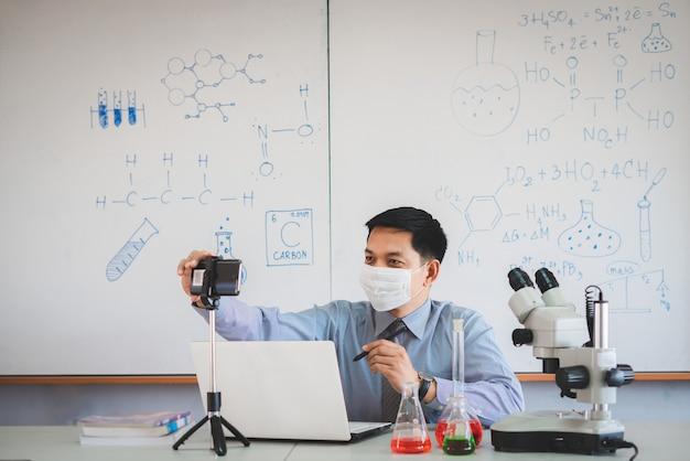 Wissenschaftslehrer, der maske trägt und online mit smartphone im klassenzimmer unterrichtet