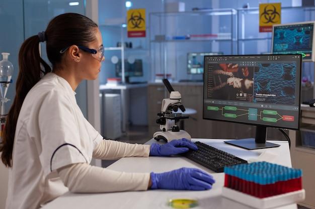 Wissenschaftsspezialist, der computer für die dna-forschung verwendet