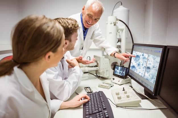 Wissenschaftsstudenten, die mikroskopisches bild auf computer mit lektor betrachten