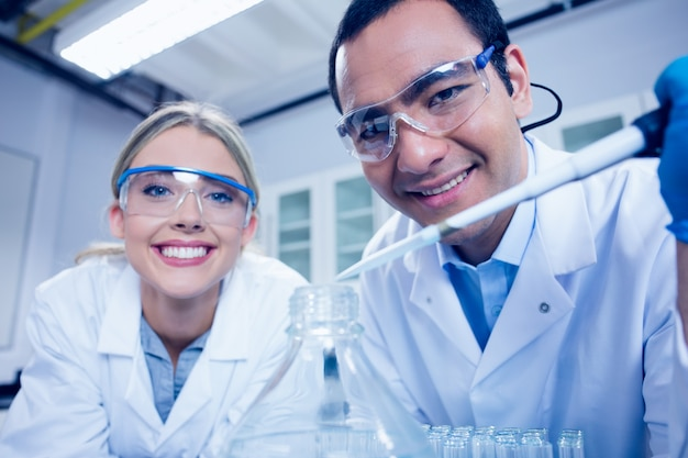 Wissenschaftsstudenten, die pipette verwenden, um becher zu füllen