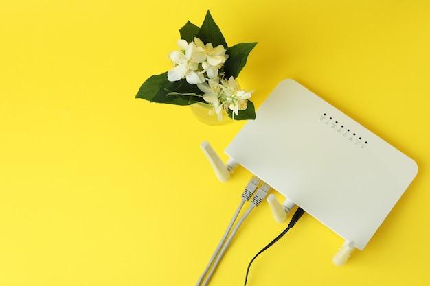 Wlan-router und blumen auf gelbem hintergrund