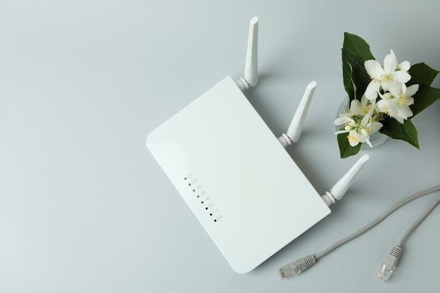 Wlan-router und blumen auf grauem hintergrund