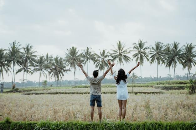 Wo paar hebt den arm, während sie reisfeld genießen
