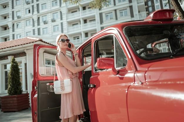 Wo sind sie. frau, die draußen steht, auf ihre tochter wartet und sie anruft, bevor sie ins auto steigt.