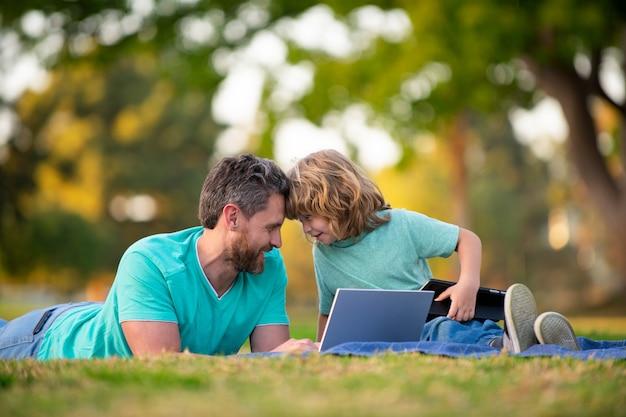 Wochenendaktivität glückliches familienlebensstilkonzept vater mit sohn verwenden laptop-vater und schuljunge-kind ...
