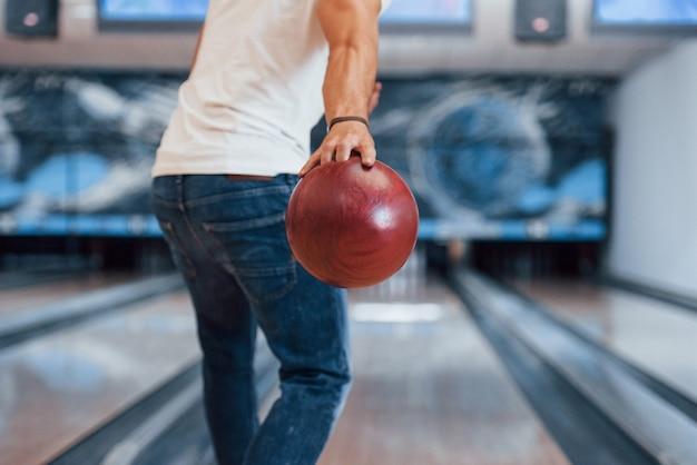 Wochenendaktivitäten. hintere partikelansicht des mannes in der freizeitkleidung, die bowling im club spielt