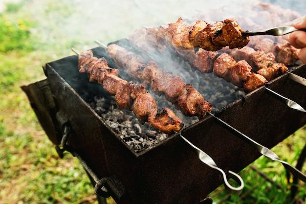 Wochenendaktivitäten mit familienkonzept, leckerer grillspieß mit schweinefleisch auf kohlenbecken mit rauch. foto in hoher qualität