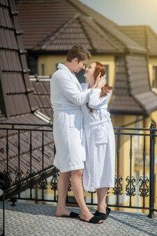 Wochenende. ein paar in weißen bademänteln genießt den morgen in einem landhaus und sieht entspannt aus