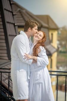 Wochenende. ein paar in weißen bademänteln genießt den morgen in einem landhaus und sieht entspannt aus Premium Fotos