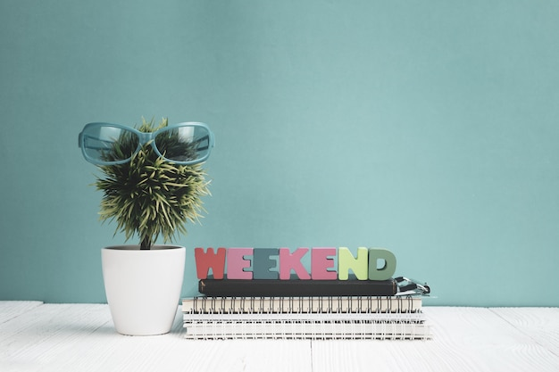 Wochenende-text und notizbuchpapier und kleiner baum auf holz