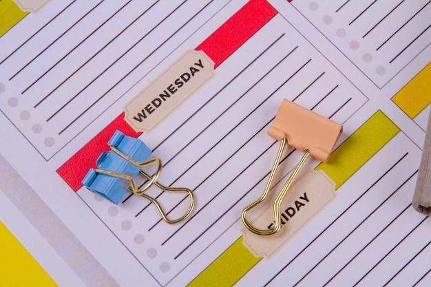 Wochenkalender und farbige binderclips nahaufnahme.