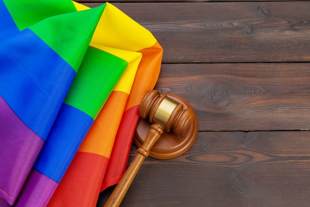 Woden-richterhammer des gesetzes und der gerechtigkeit mit lgbt-flagge in den regenbogenfarben auf hölzernem hintergrund