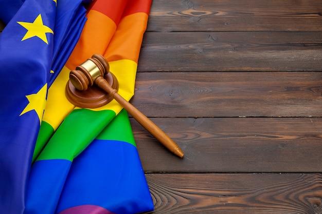 Woden-richterholzhammer-symbol des gesetzes und der gerechtigkeit mit lgbt-flagge in den regenbogenfarben auf hölzernem