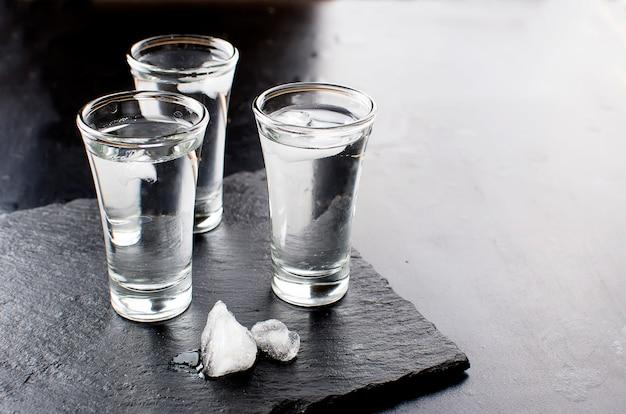 Wodka-aufnahmen auf schwarzen tisch