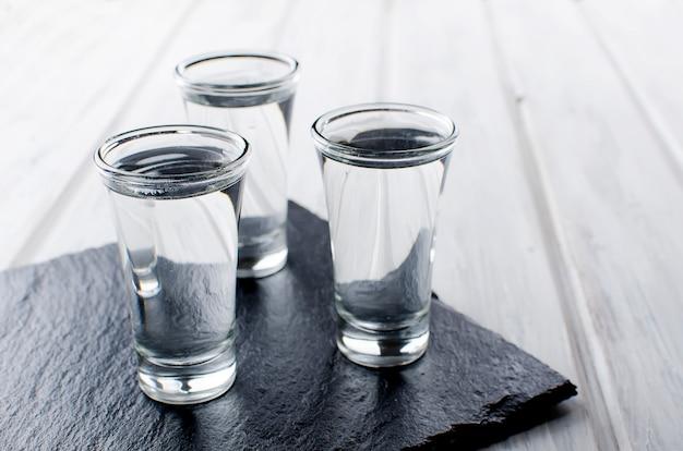 Wodka-aufnahmen auf weißen tisch