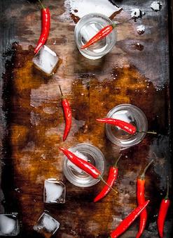 Wodka-aufnahmen mit chili-pfeffer auf einem holztisch.