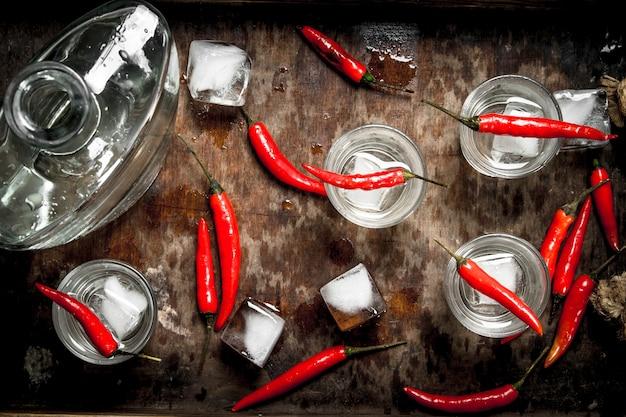 Wodka-aufnahmen mit chilischoten auf einem holztablett auf einem rustikalen tisch.