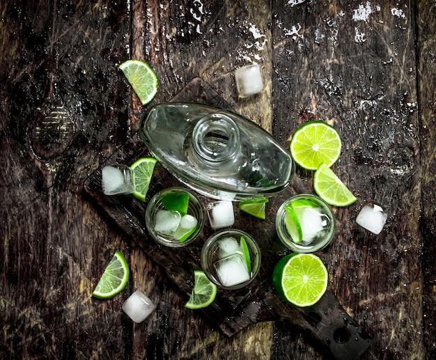 Wodka-aufnahmen mit limette und eis auf dem brett auf einem holztisch.