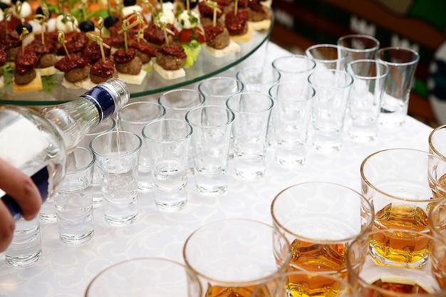 Wodka gießt aus einer flasche in einem schuss, der auf dem weißen tisch steht