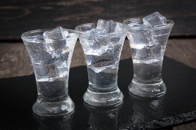 Wodka glas mit eis auf holztisch.