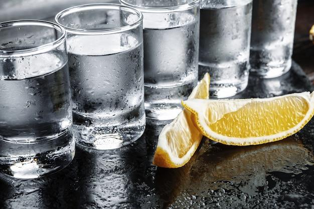 Wodka in den schnapsgläsern auf rustikalem hölzernem hintergrund