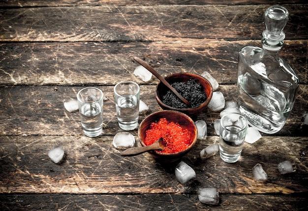 Wodka in einer flasche mit schwarzem und rotem kaviar. auf hölzernem hintergrund.