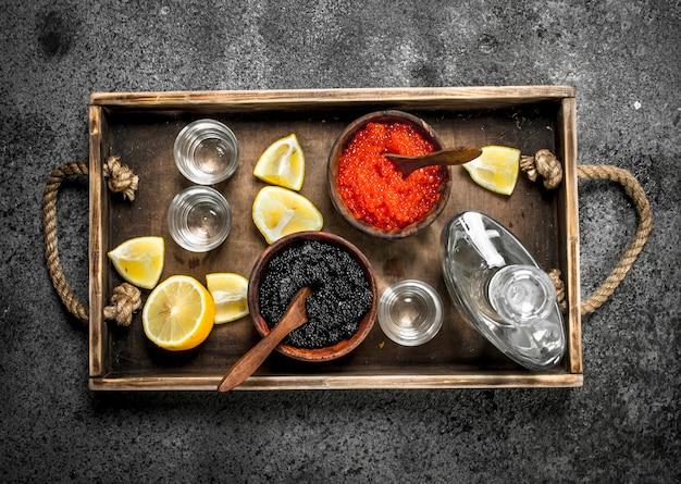 Wodka in einer flasche mit schwarzem und rotem kaviar. auf rustikalem hintergrund.