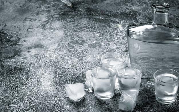 Wodka mit eis in gläsern auf einem rustikalen tisch.