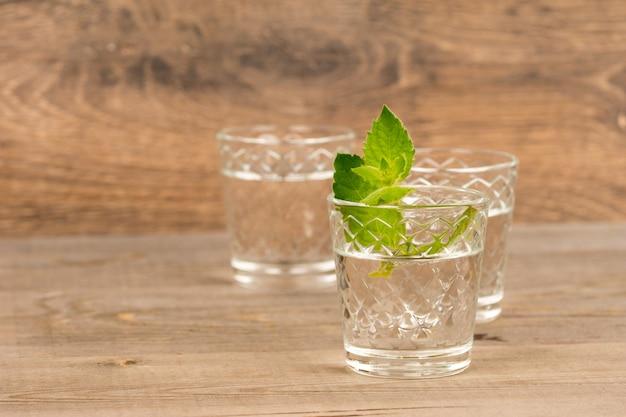 Wodka mit minze in schnapsgläsern auf rustikalem holztisch