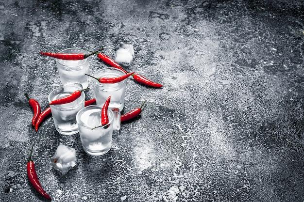 Wodka-shots mit peperoni auf einem rustikalen tisch.
