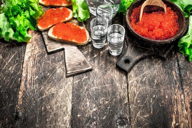 Wodka und sandwiches mit rotem kaviar auf holztisch.
