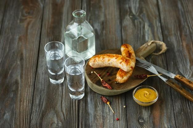 Wodka und traditioneller snack auf holzwand