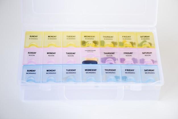 Wöchentlicher plastikpillenorganisator mit pillen auf weißem hintergrund