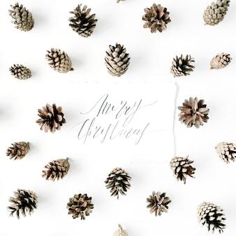 Wörter frohe weihnachten und minimales kreatives kegelanordnungsmuster auf weiß.