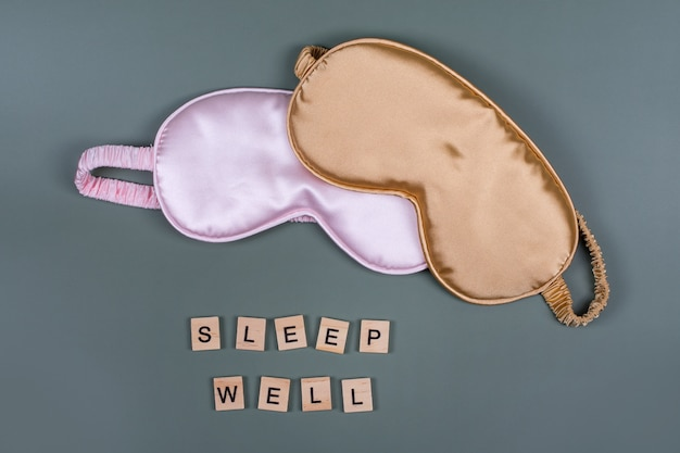 Wörter sleep well und schlafende augenmasken, draufsicht, gute nacht, flug- und reisekonzept