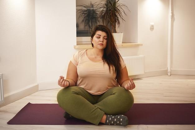 Wohlbefinden, harmonie, yoga, meditation, zen und entspannung. übergewichtige mollige junge frau sitzt auf der matte, schließt die augen und hält die beine gekreuzt, meditiert und sucht nach innerem frieden und gleichgewicht