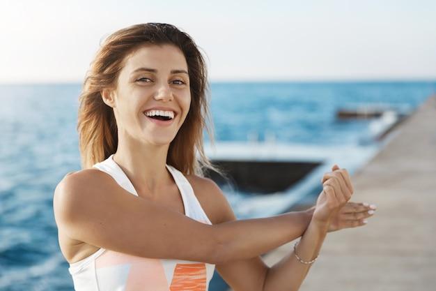 Wohlbefinden, sport-lifestyle-konzept. glücklicher freudiger junger weiblicher athlet, der arme lehnt, die im pier lachen