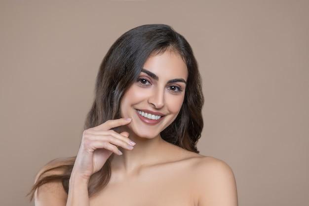 Wohlbefinden, stimmung. lächelnde langhaarige junge frau mit nackten schultern, die hand zum schönen gesicht berühren