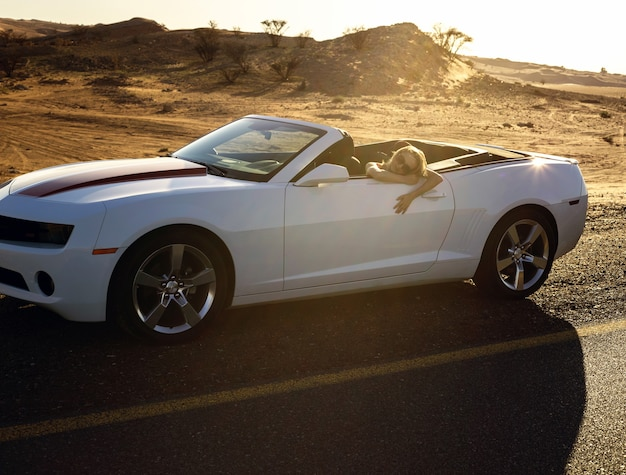 Wohlhabende frau während der fahrt in der wüste mit dem cabrio