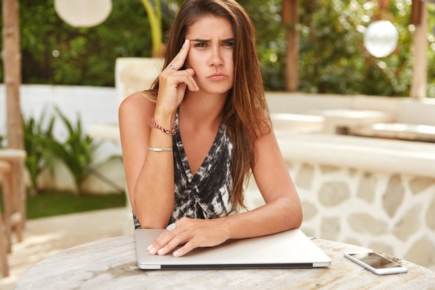 Wohlhabende junge geschäftsfrau, die sich in den tropen erholt, immer in kontakt ist, geschäftliche angelegenheiten auf distanz regelt, von modernen elektronischen geräten umgeben ist, müde aussieht und sich gegen ein straßencafé ausgibt