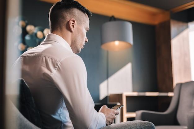 Wohlhabender geschäftsmann. junger, aber wohlhabender geschäftsmann, der in seinem büro mit telefon sitzt