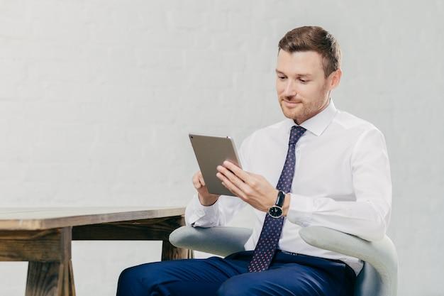 Wohlhabender gutaussehender mann passt webinar online auf modernem tablet-computer auf